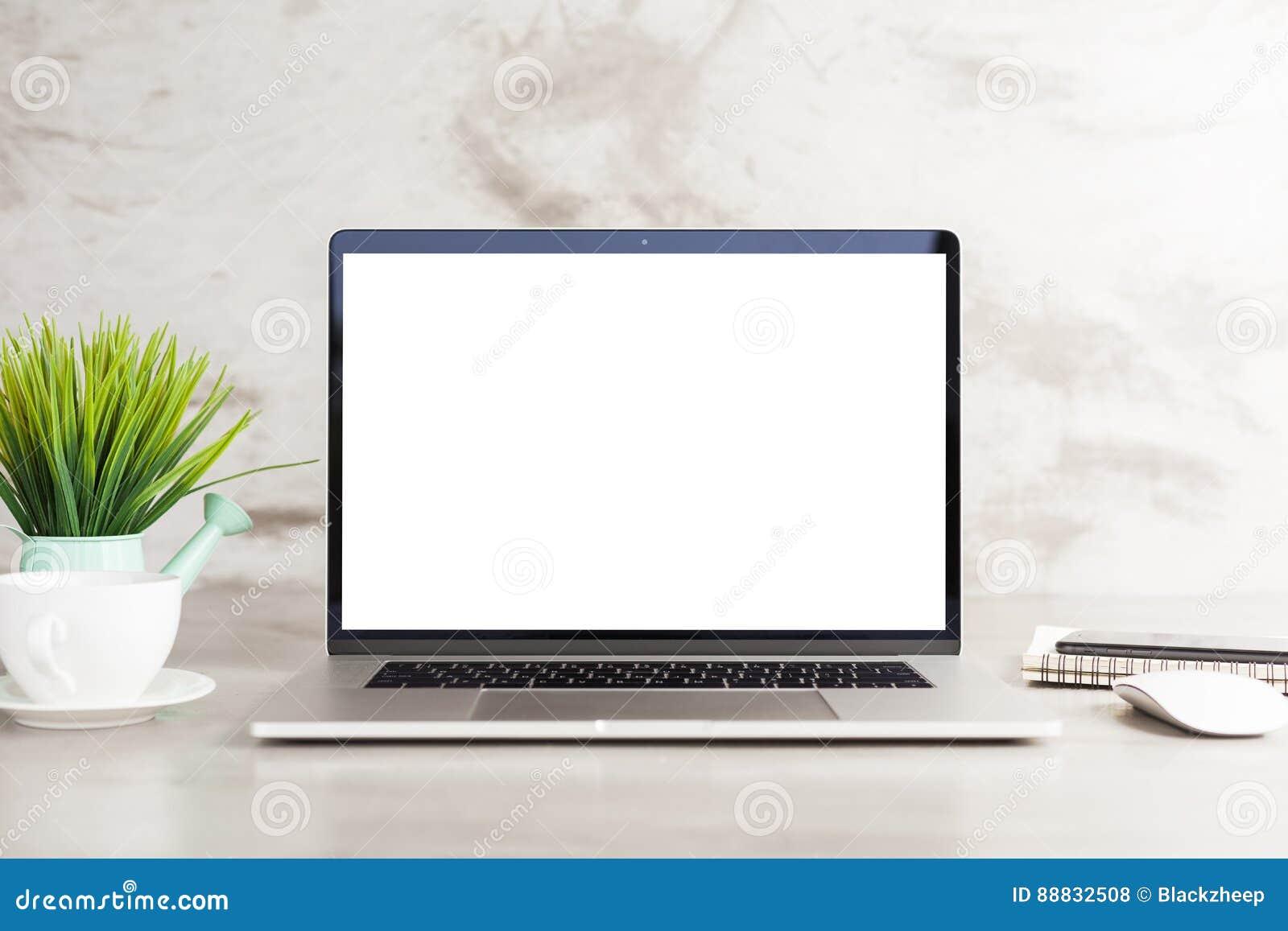 Écran vide blanc d ordinateur portable sur la vue de face de table de travail