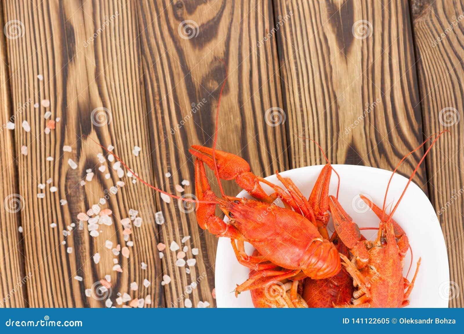 Écrevisses rouges bouillies en cuvette en céramique blanche et sel dispersé