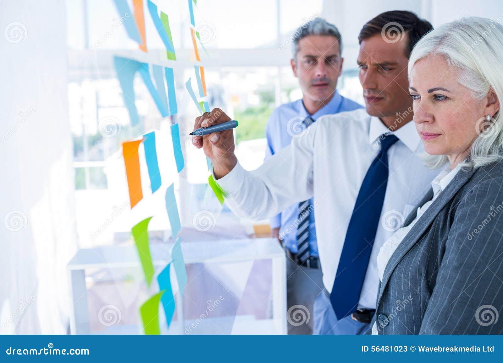 Écriture d homme d affaires sur le post-it avec ses collègues