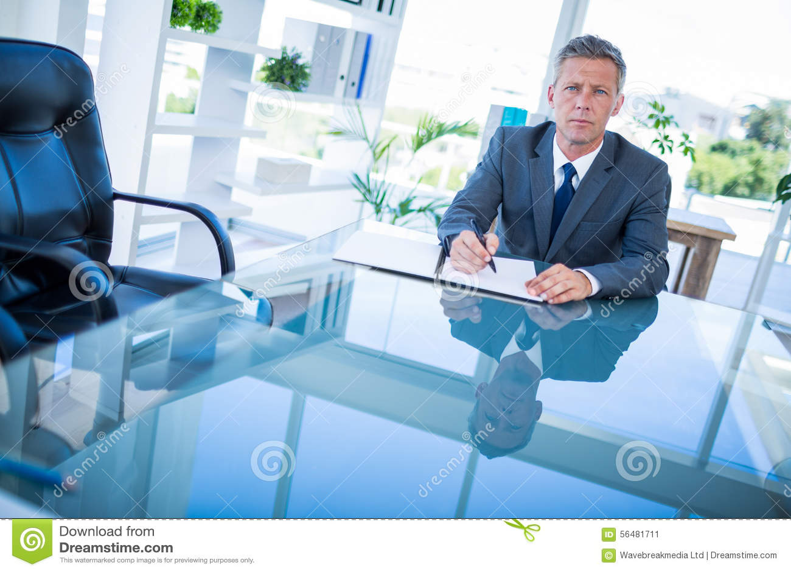 Écriture d homme d affaires sur le presse-papiers et regarder l appareil-photo