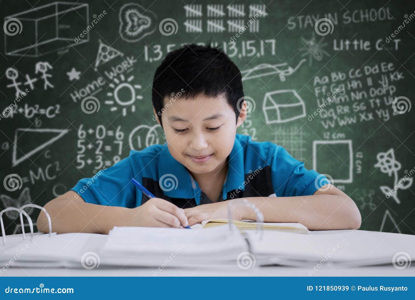Écriture de la préadolescence belle de garçon dans la salle de classe