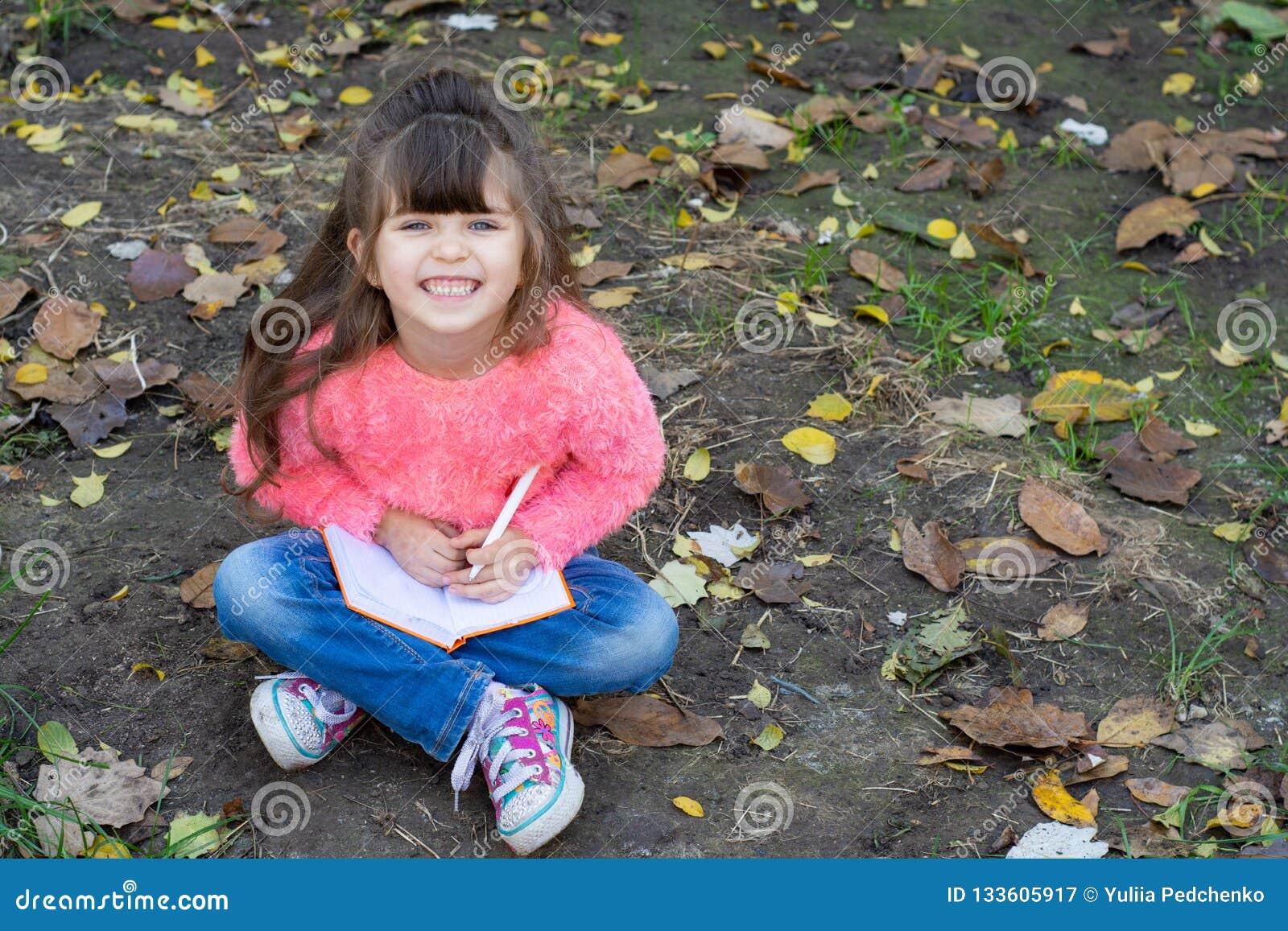 Écriture drôle d enfant dans le carnet utilisant le stylo et le sourire Quatre années badinent se reposer sur l herbe,