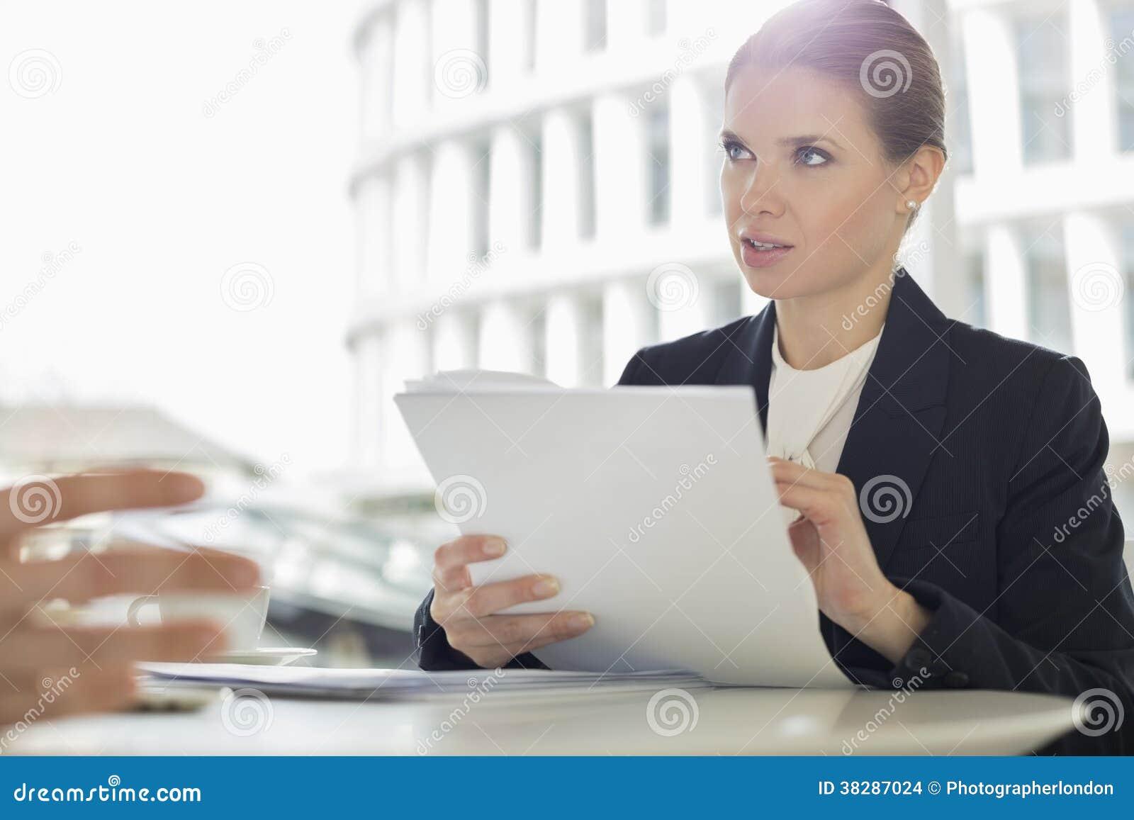 Écritures de discussion de femme d affaires avec le collègue dans le cafétéria de bureau