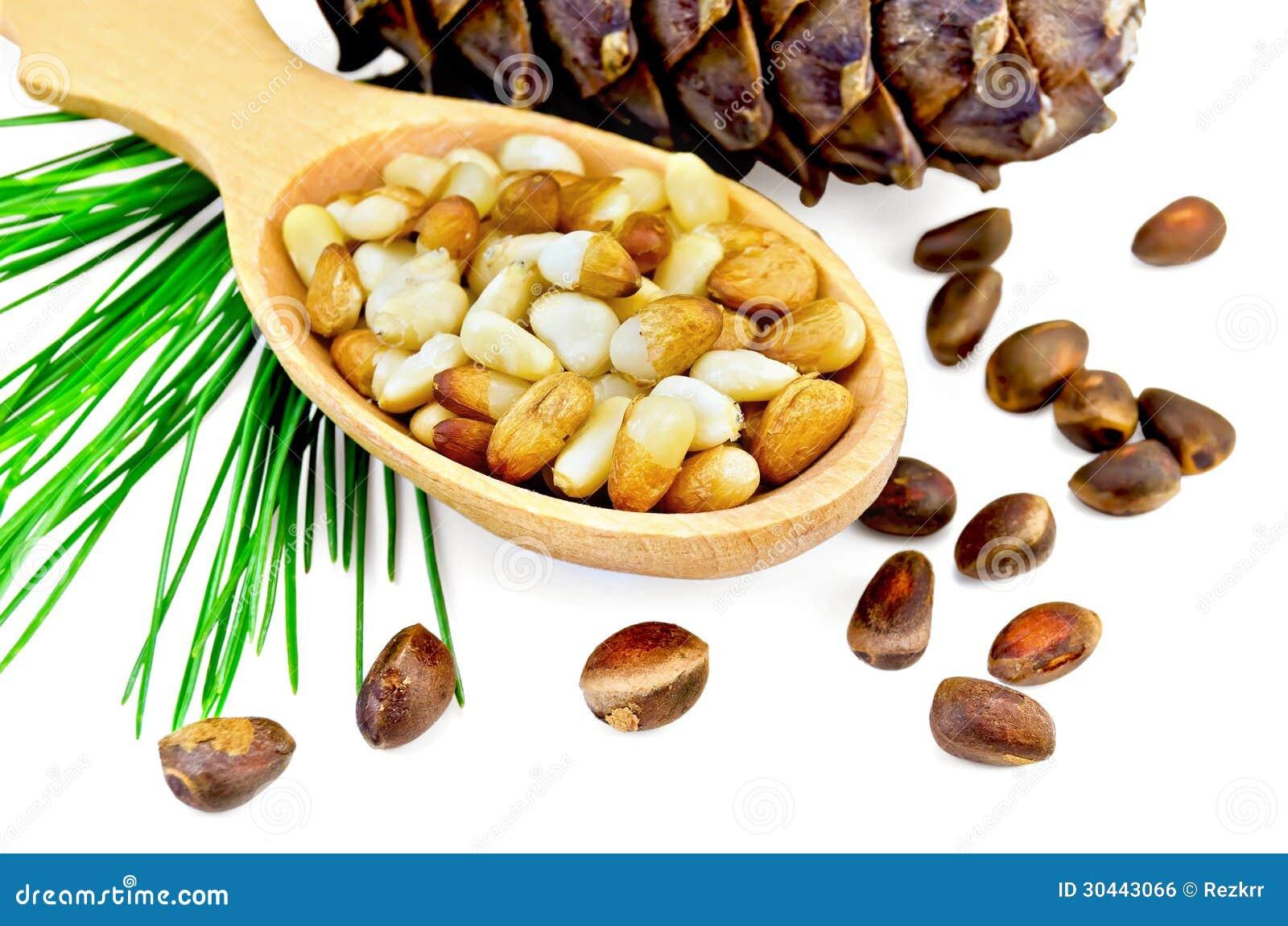 Écrous de cèdre dans une cuillère en bois et une bosse