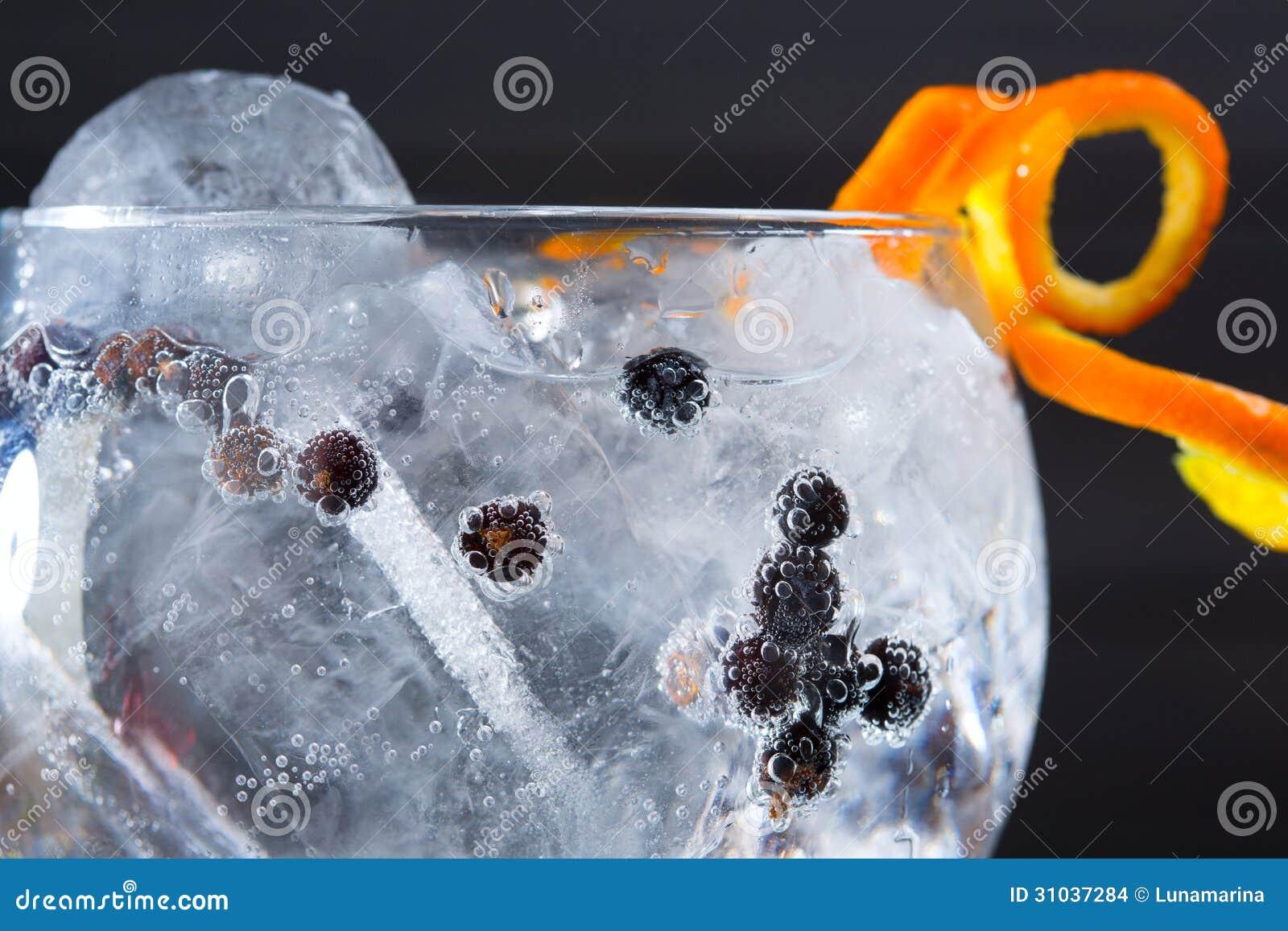 Égrenez le macro plan rapproché de cocktail tonique avec des baies de genévrier
