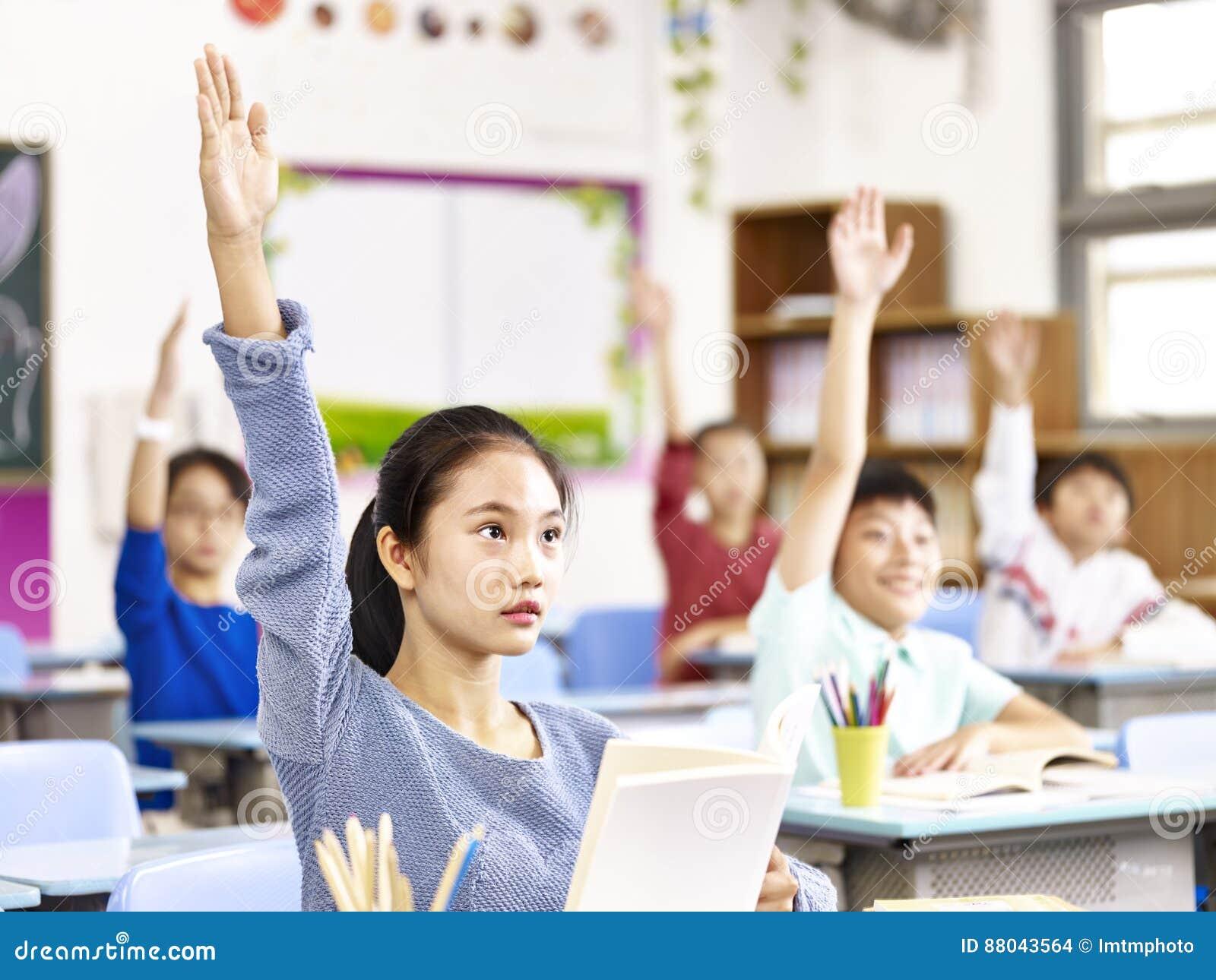 Élève asiatique soulevant des mains dans la salle de classe