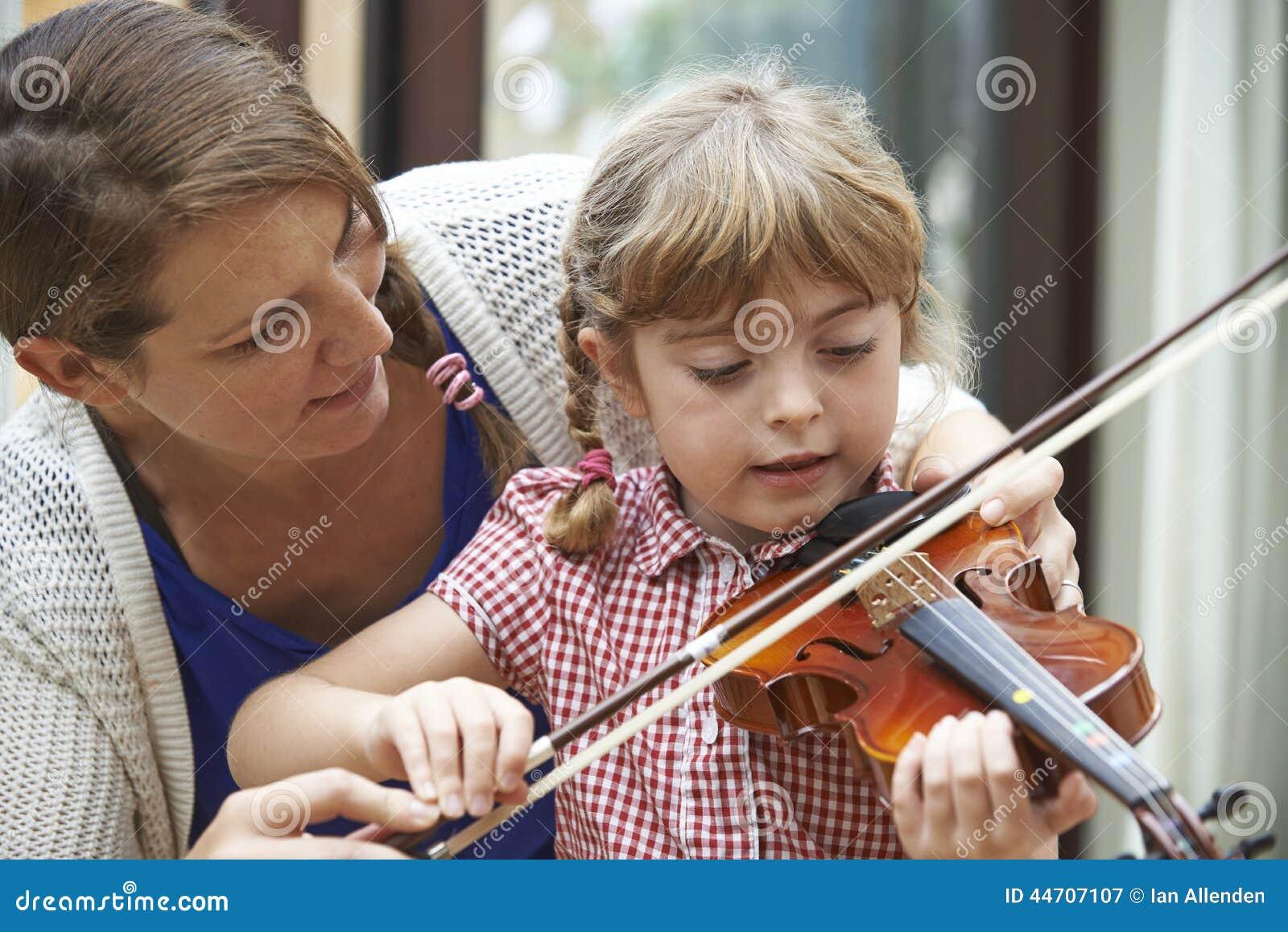 Élève de Helping Young Female de professeur dans la leçon de violon