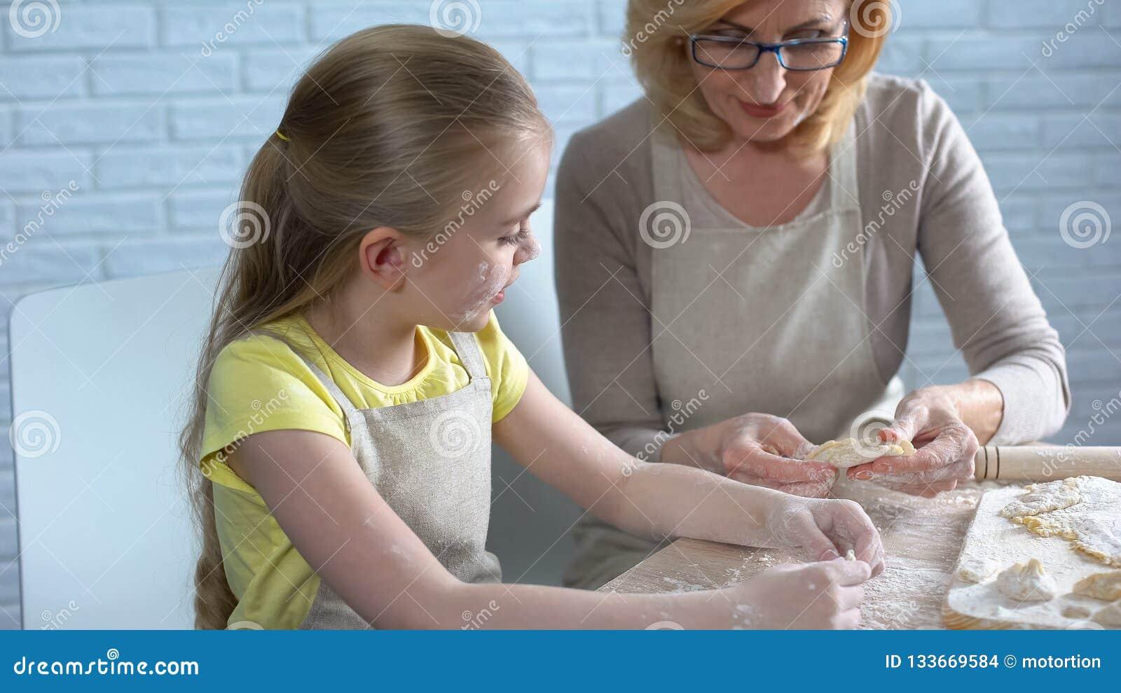 Élève du cours préparatoire assez féminin essayant de faire cuire la pâtisserie, aidant sa mamie dans la cuisine