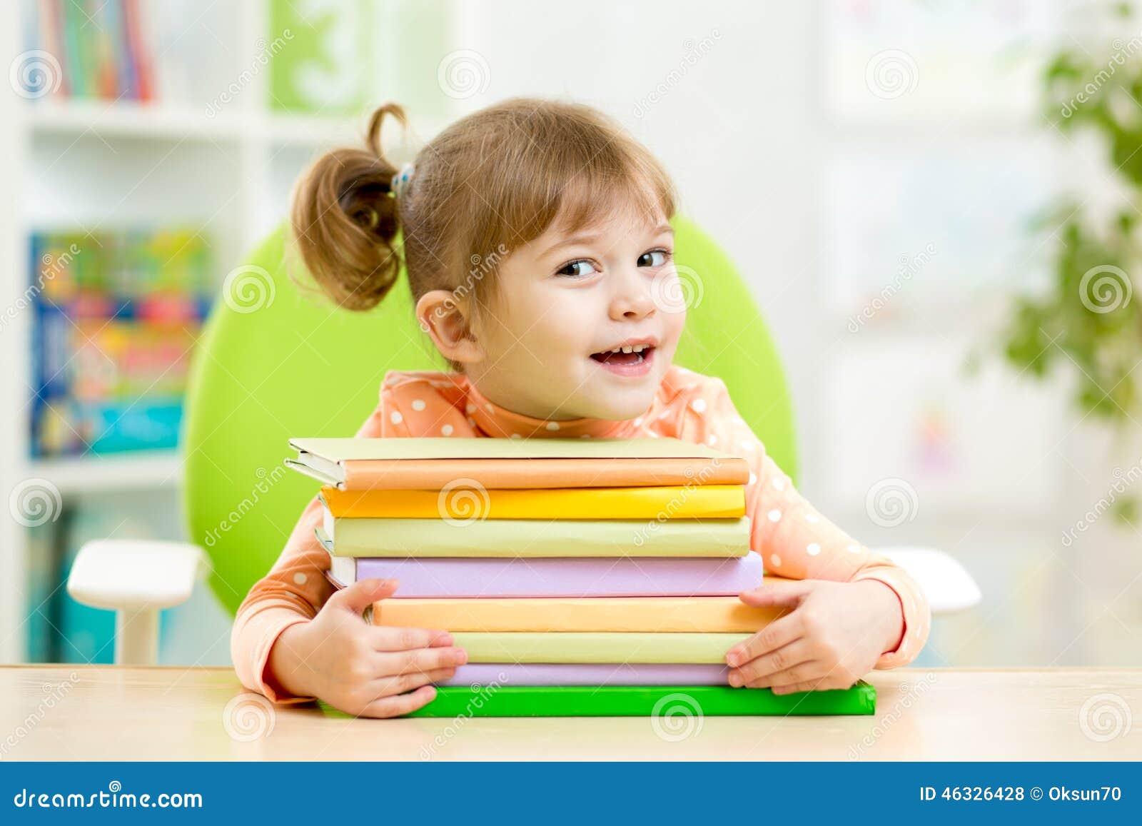 Élève du cours préparatoire futé de fille d enfant avec des livres