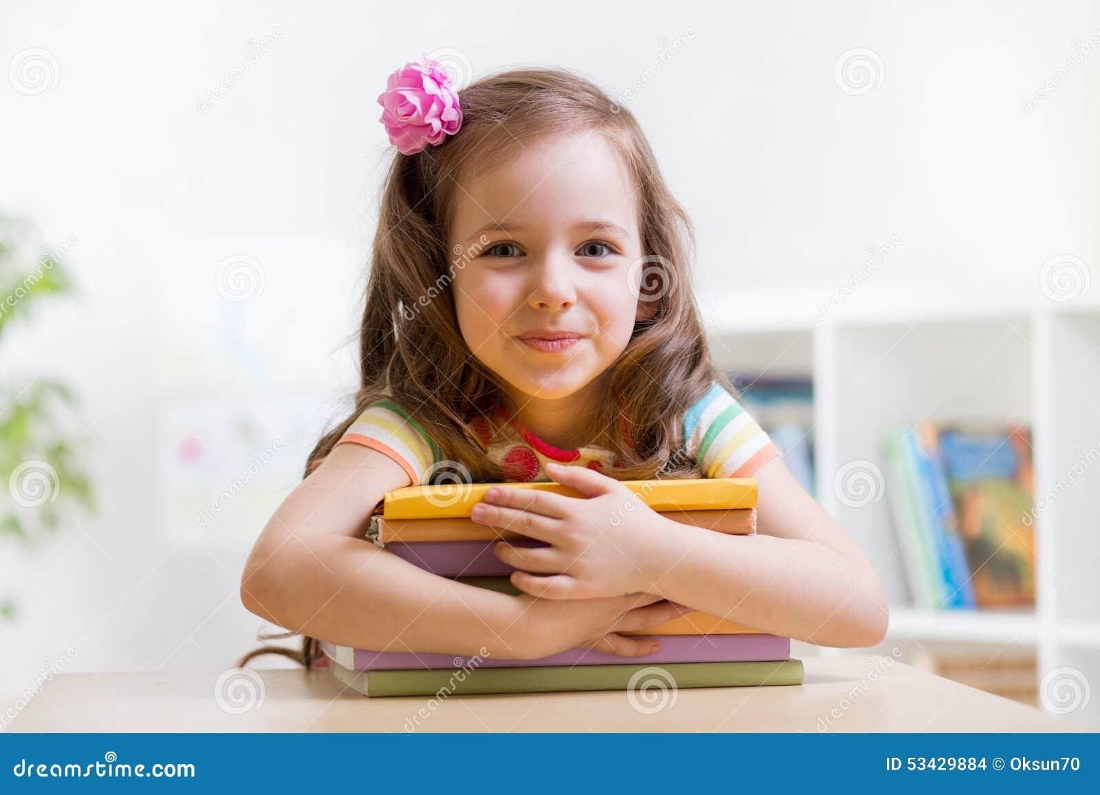 Élève du cours préparatoire mignon de fille d enfant avec des livres