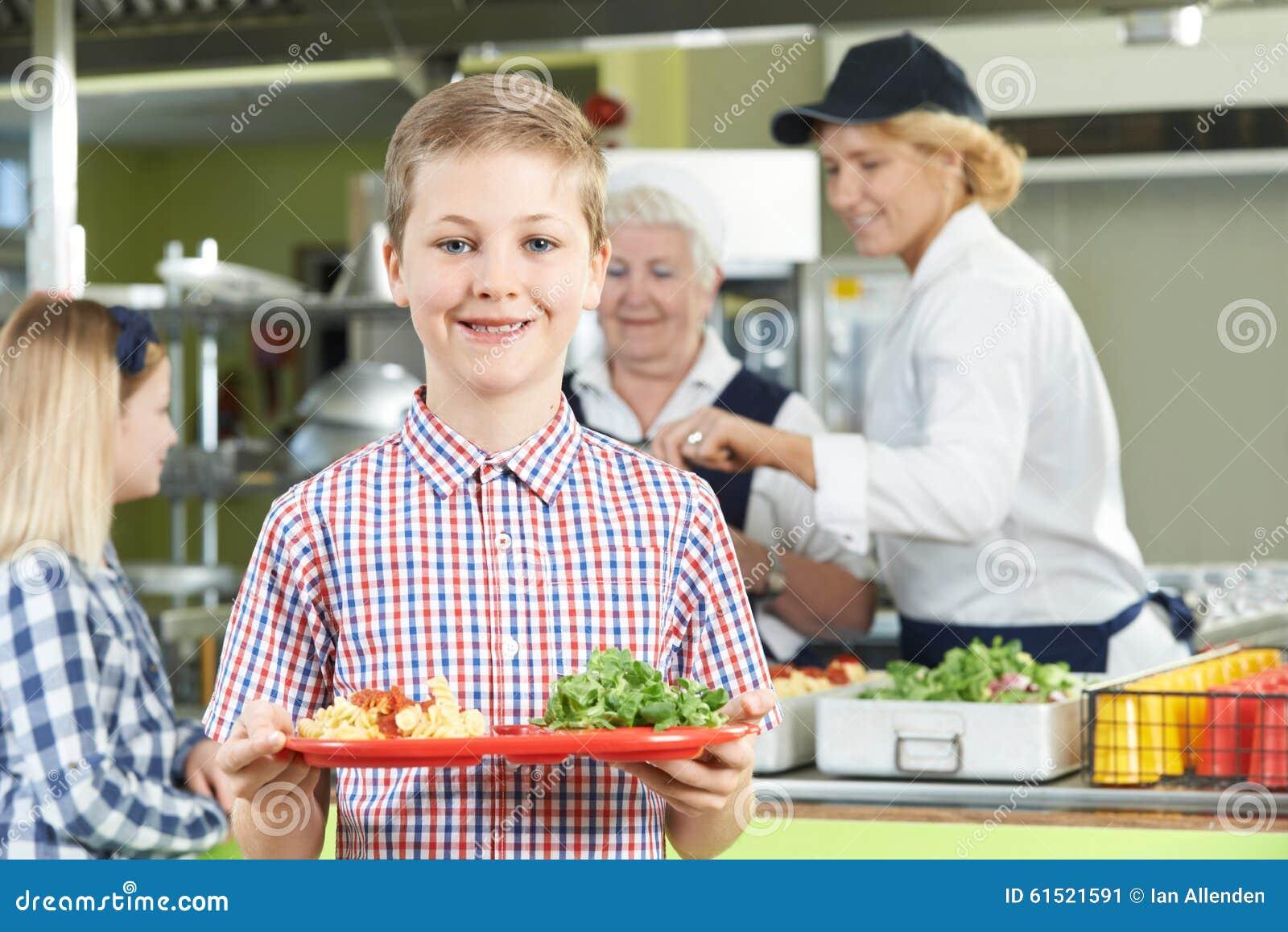 Élève masculin avec le déjeuner sain dans la cantine scolaire