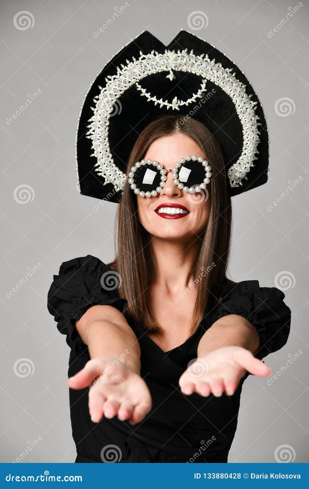 Élégance et type Portrait de studio de jeune femme magnifique dans peu de robe noire posant sur le fond gris