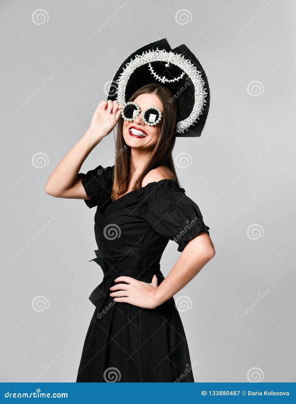 Élégance et type Portrait de studio de jeune femme magnifique dans peu de robe noire posant sur le fond jaune