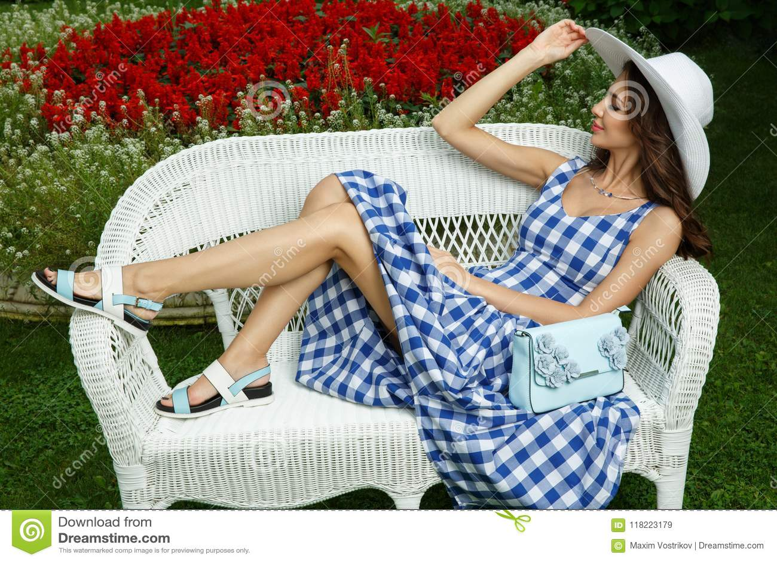 Élégante, assez et la belle jeune dame est se trouvante et posante sur le sofa en osier en parc naturel