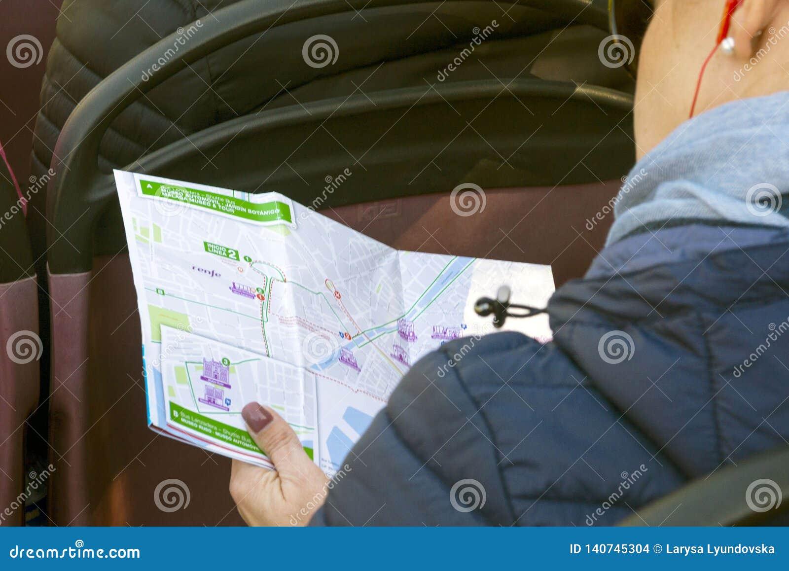 Él muchacha se sienta en el bus turístico, auriculares que llevan, escucha la historia de la guía y considera el mapa de Málaga