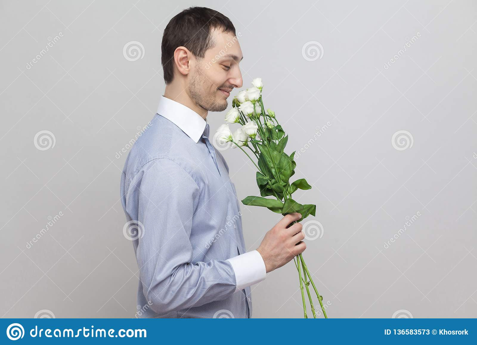 Él quiere dar las flores Retrato de la vista lateral del hombre joven romántico del placer encantador en ramo azul de la tenencia