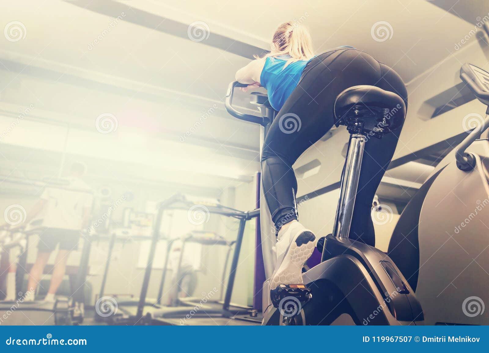 Élaboration active de jeune femme, faisant le sport faisant du vélo dans le gymnase pour la forme physique Formation sportive de
