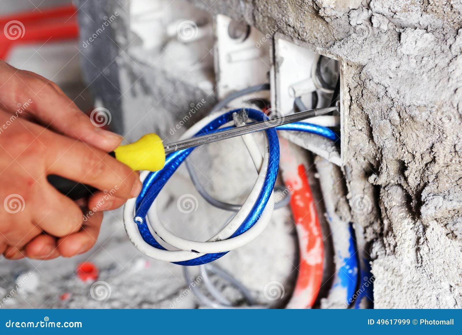 Électricien installant une prise de commutateur