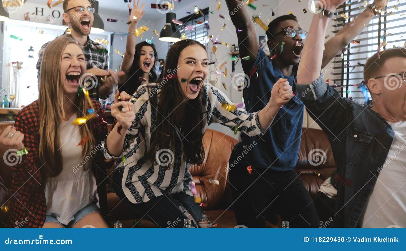 émotion Les fans multi-ethniques célèbrent le gain Mouvement lent des confettis 4K Jeu de observation de cri passionné de défense