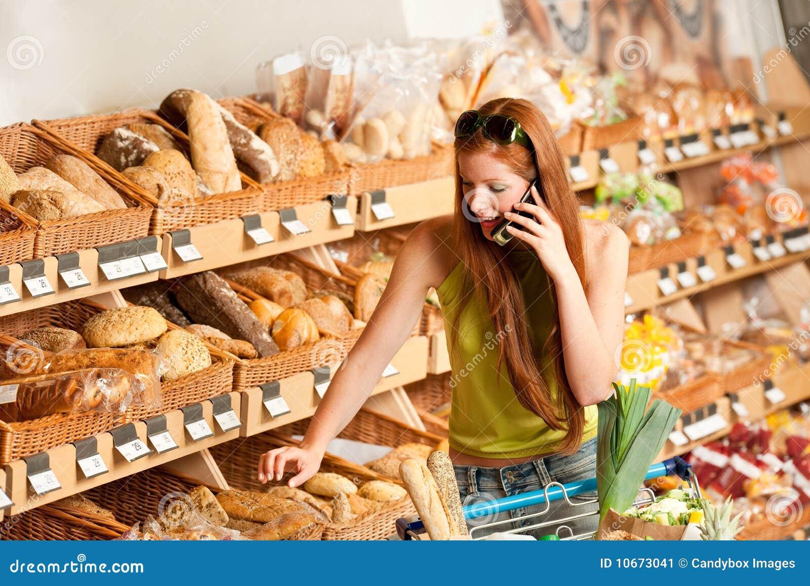 Épicerie : Femme rouge de cheveu avec le téléphone portable