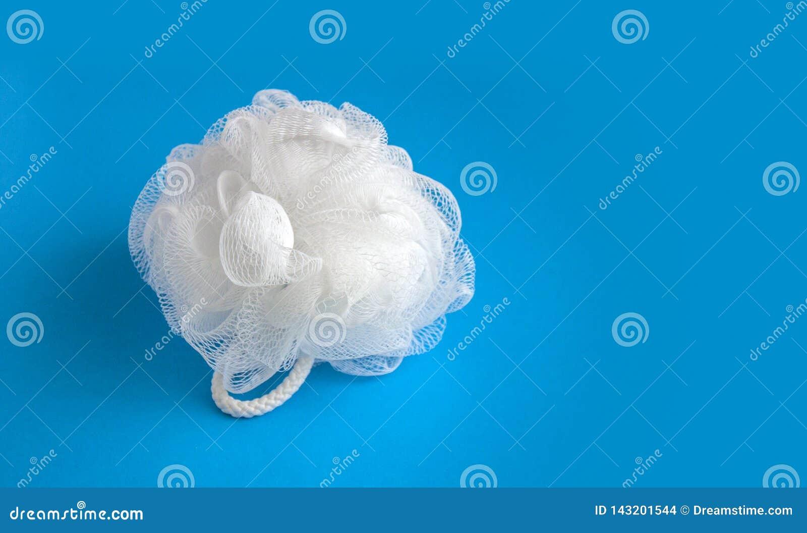 Éponge blanche de bain sur le fond bleu