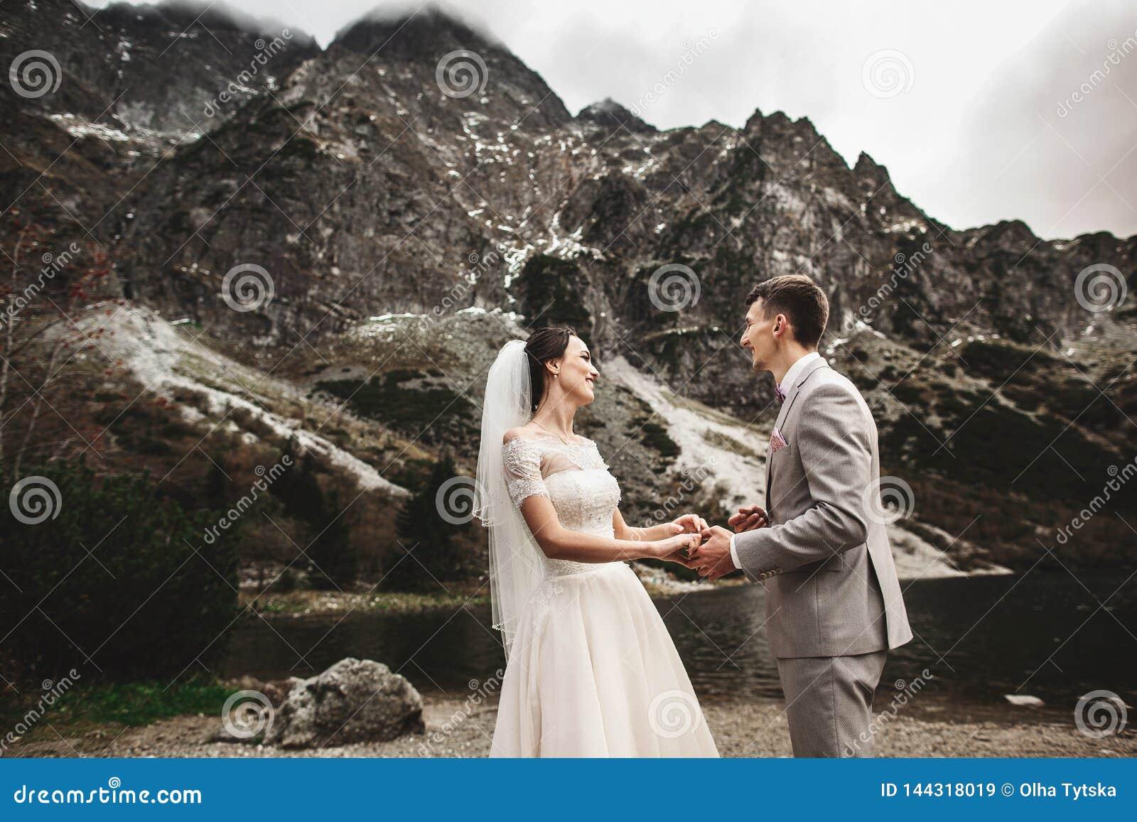?pousant des couples marchant et tenant des mains sur le rivage de lac Jour ensoleill? en montagnes de Tatra