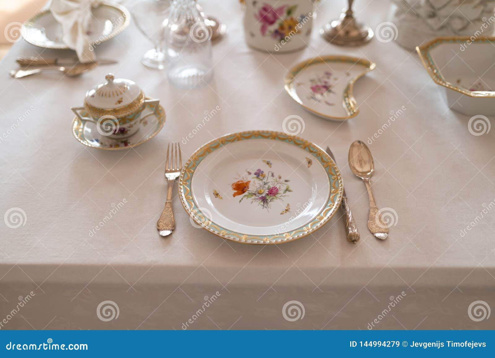 Épouser la décoration de table avec de rétros plats et couverts royaux chers de service de porcelaine de majesté dans un pala