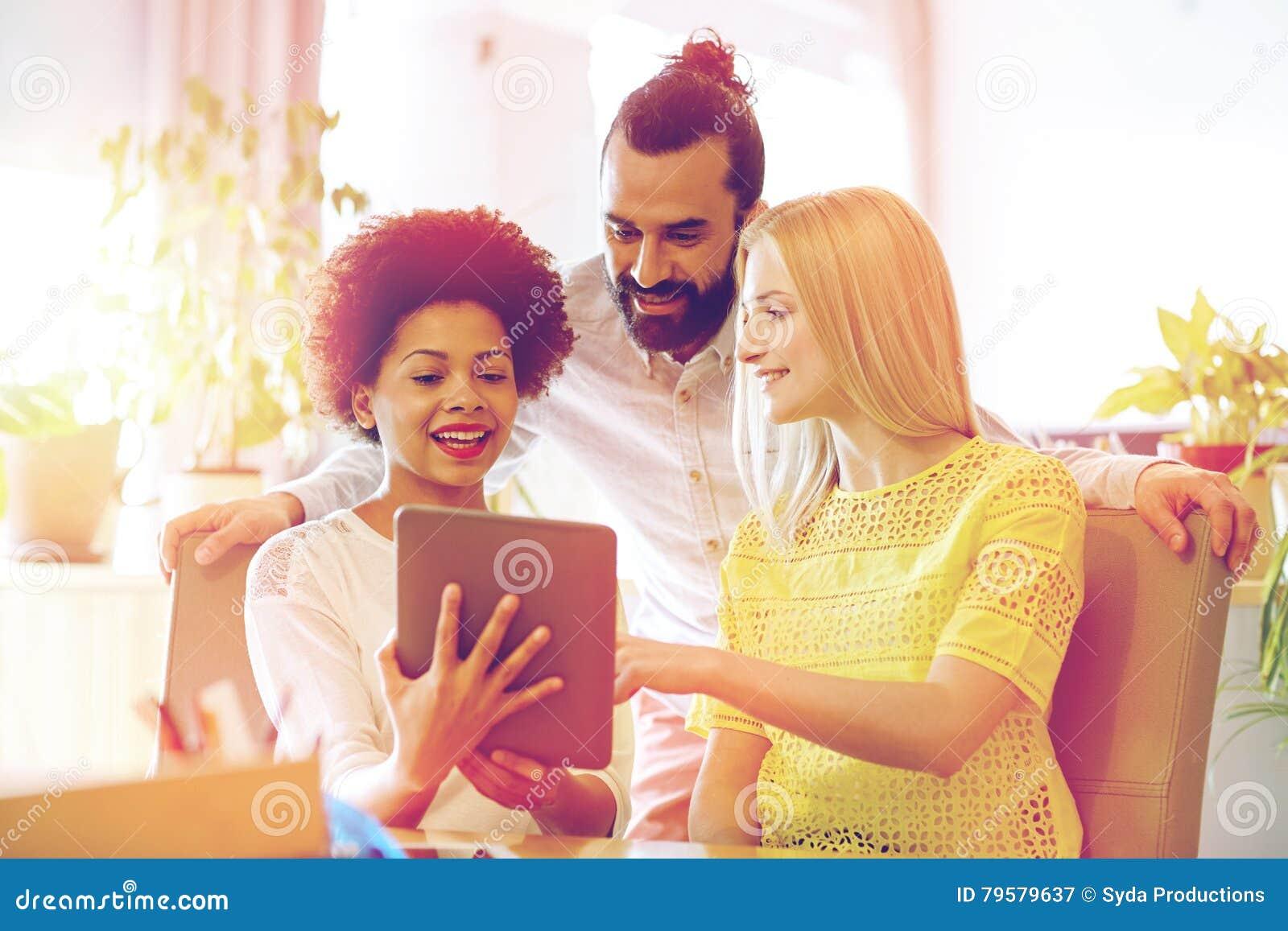 Équipe créative heureuse avec le pc de comprimé dans le bureau image