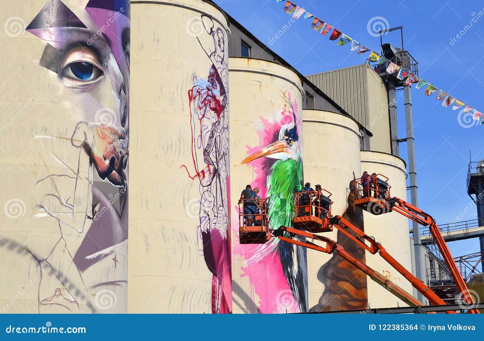 Équipe d artistes peignant des peintures murales sur des silos dans la zone idustrial