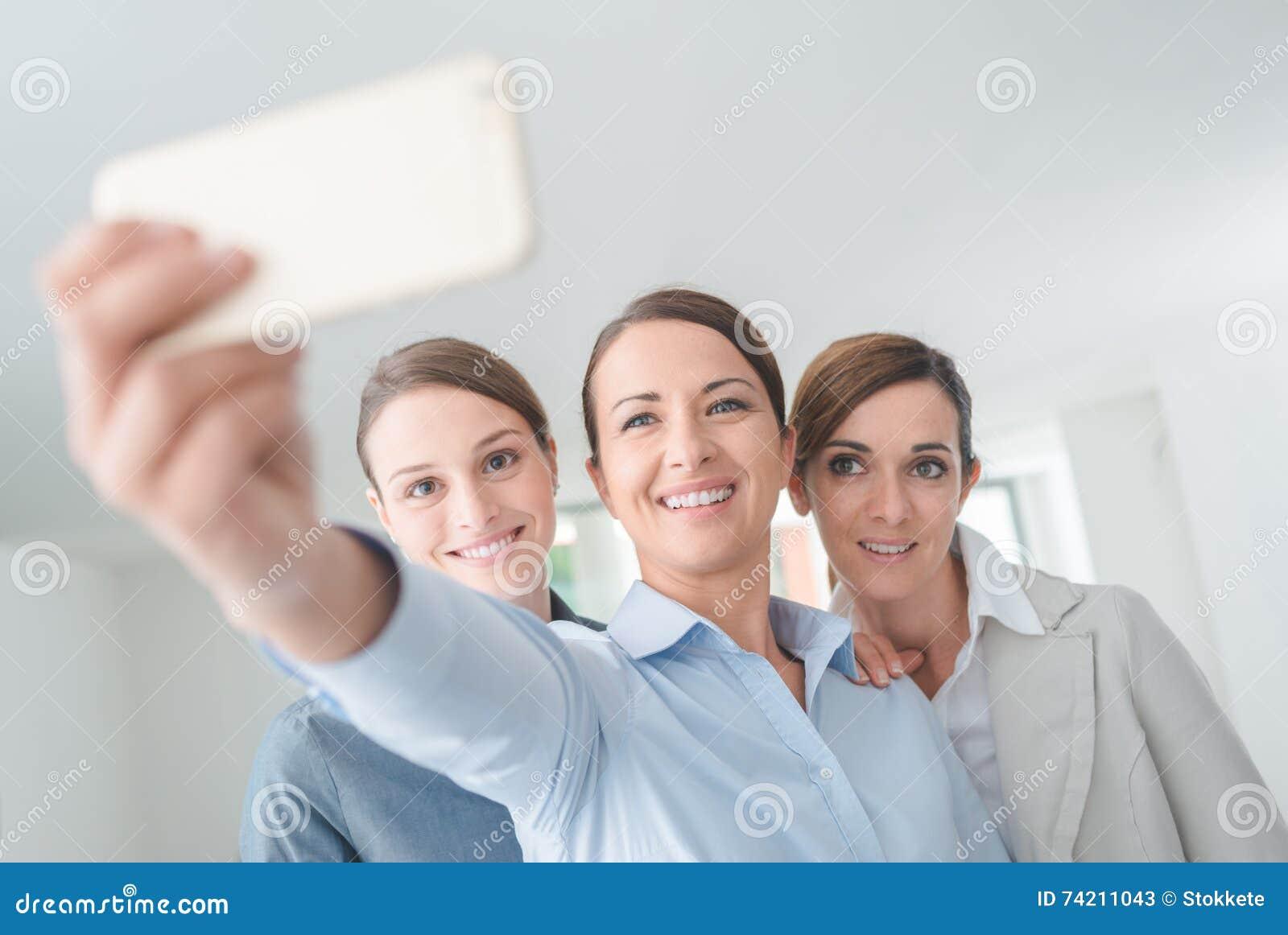 Équipe de femmes de sourire d affaires prenant un selfie