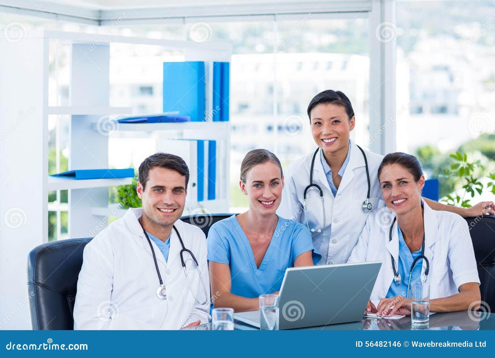 Équipe de médecins souriant à l appareil-photo