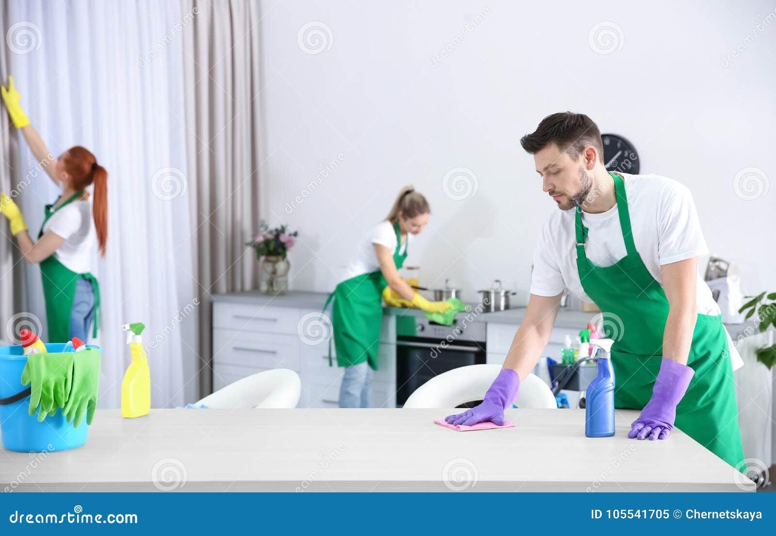 Équipe de service de nettoyage travaillant dans la cuisine