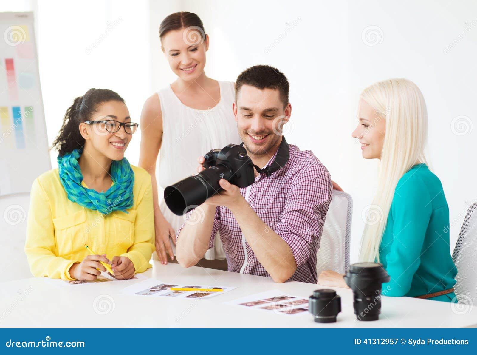 Équipe de sourire avec le photocamera fonctionnant dans le bureau