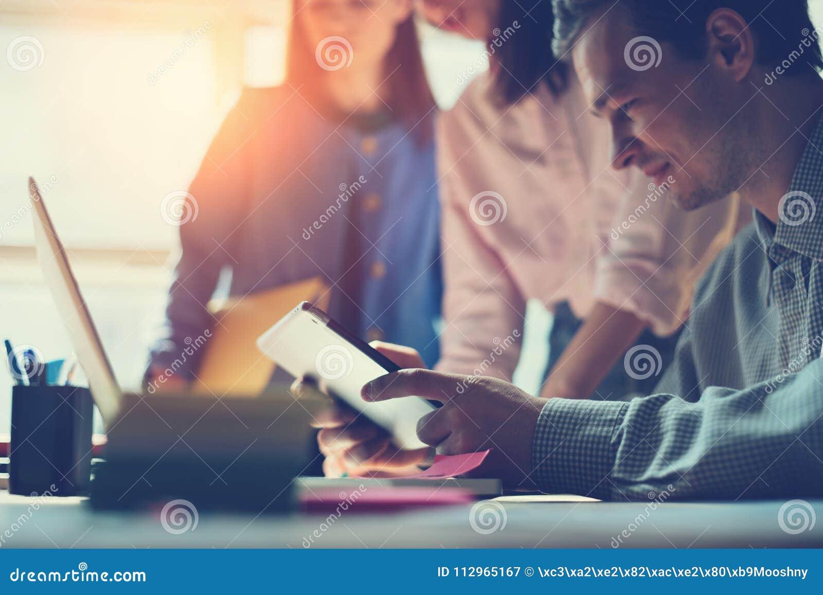 Équipe de vente discutant le nouveau plan de travail Ordinateur portable et écritures dans le bureau de l espace ouvert Homme s a
