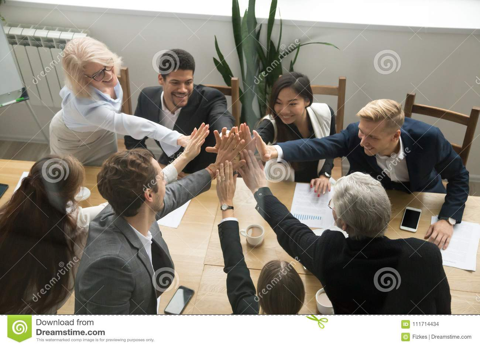 Équipe diverse d affaires donnant l unité de représentation de la haute cinq, vue supérieure