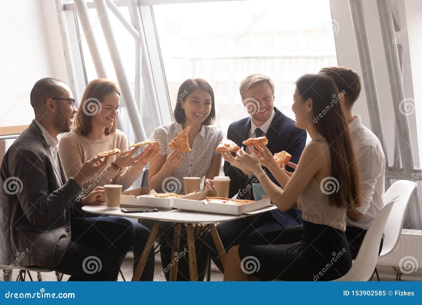 Équipe ethnique multi amicale heureuse ayant l amusement mangeant de la pizza ensemble