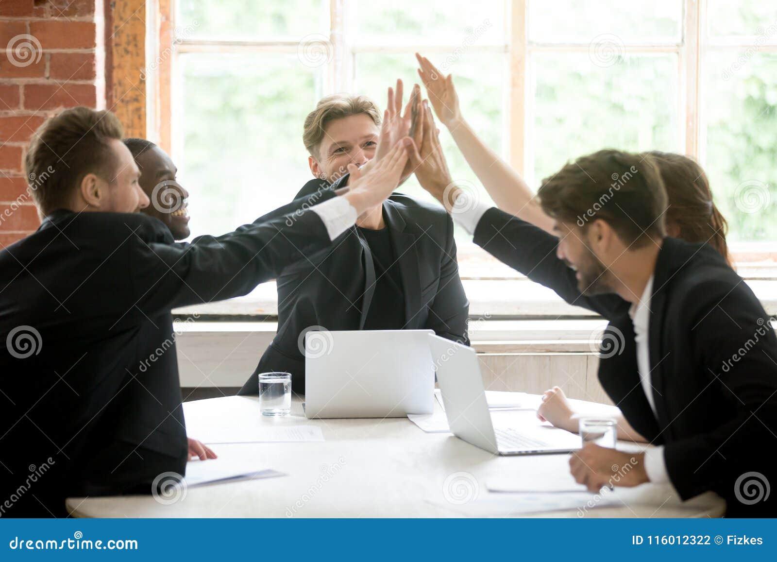 Équipe heureuse de travail donnant la haute cinq après affaire fermante d affaires