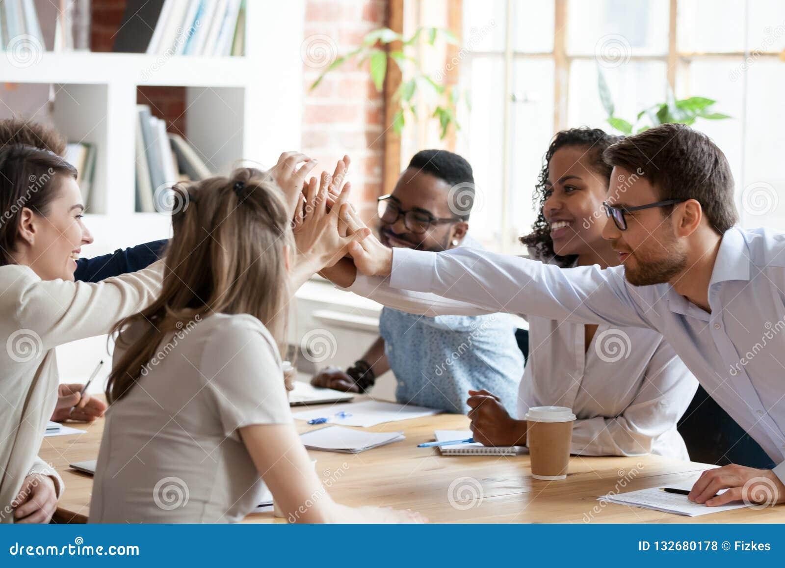 Équipe multiraciale enthousiaste donnant haut cinq lors de la réunion de société