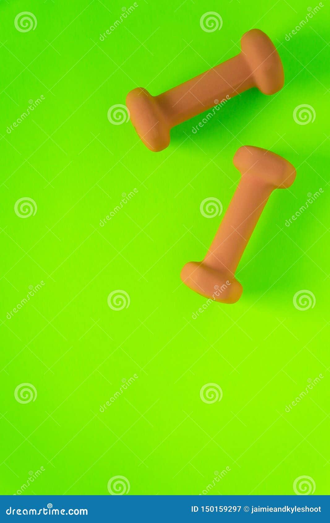 Équipement de forme physique avec les haltères jaune-orange des poids des femmes d isolement sur un vert de chaux avec le fond de
