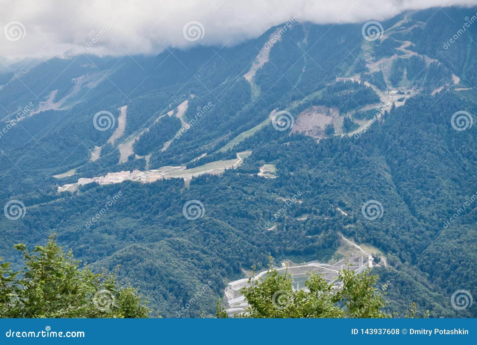 Équipements de sports et bâtiments résidentiels sur la pente d une haute montagne avec une pente verte et le dessus dans les nuag