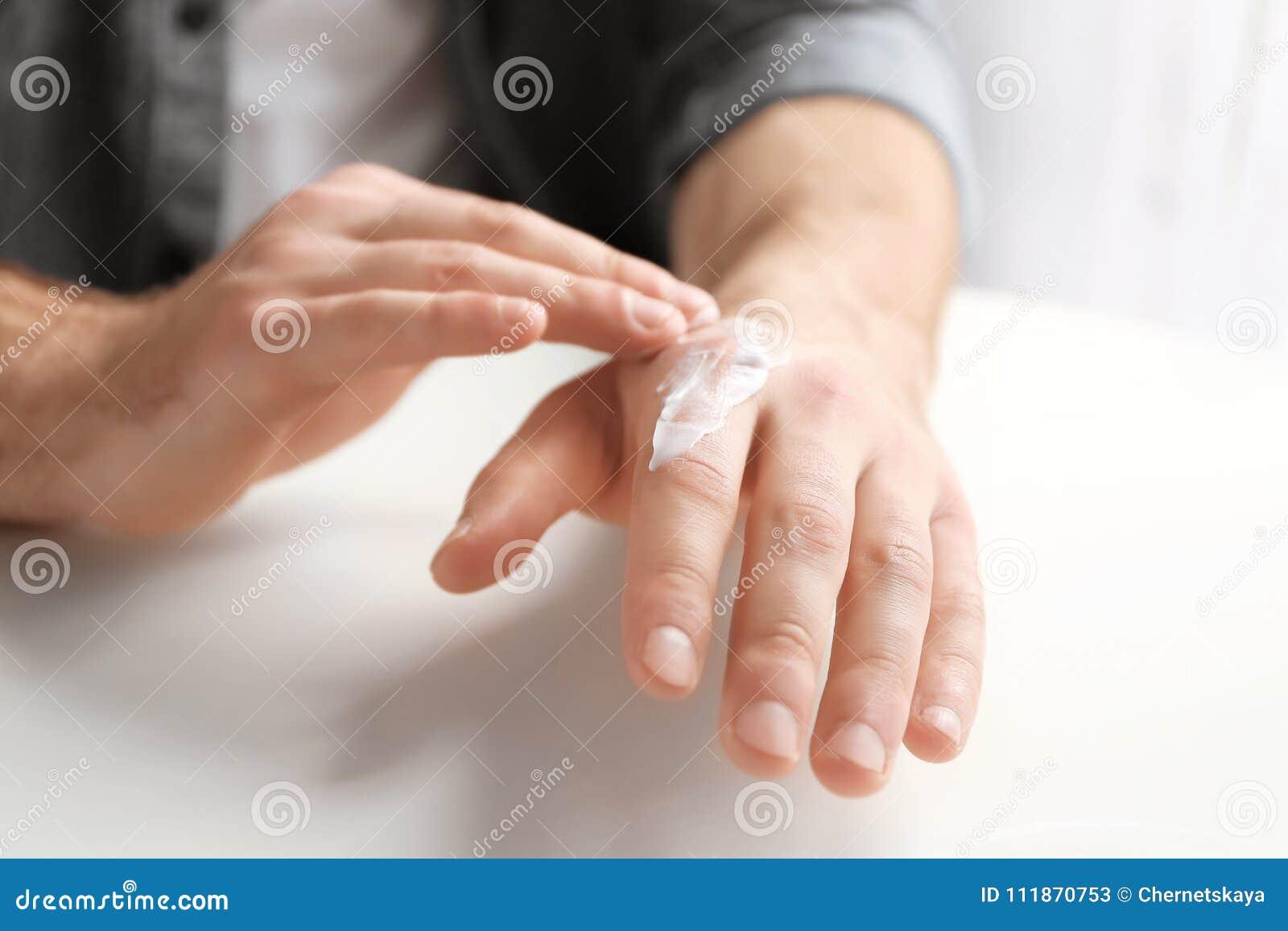 Équipez appliquer la lotion du beurre de cacao sur la main