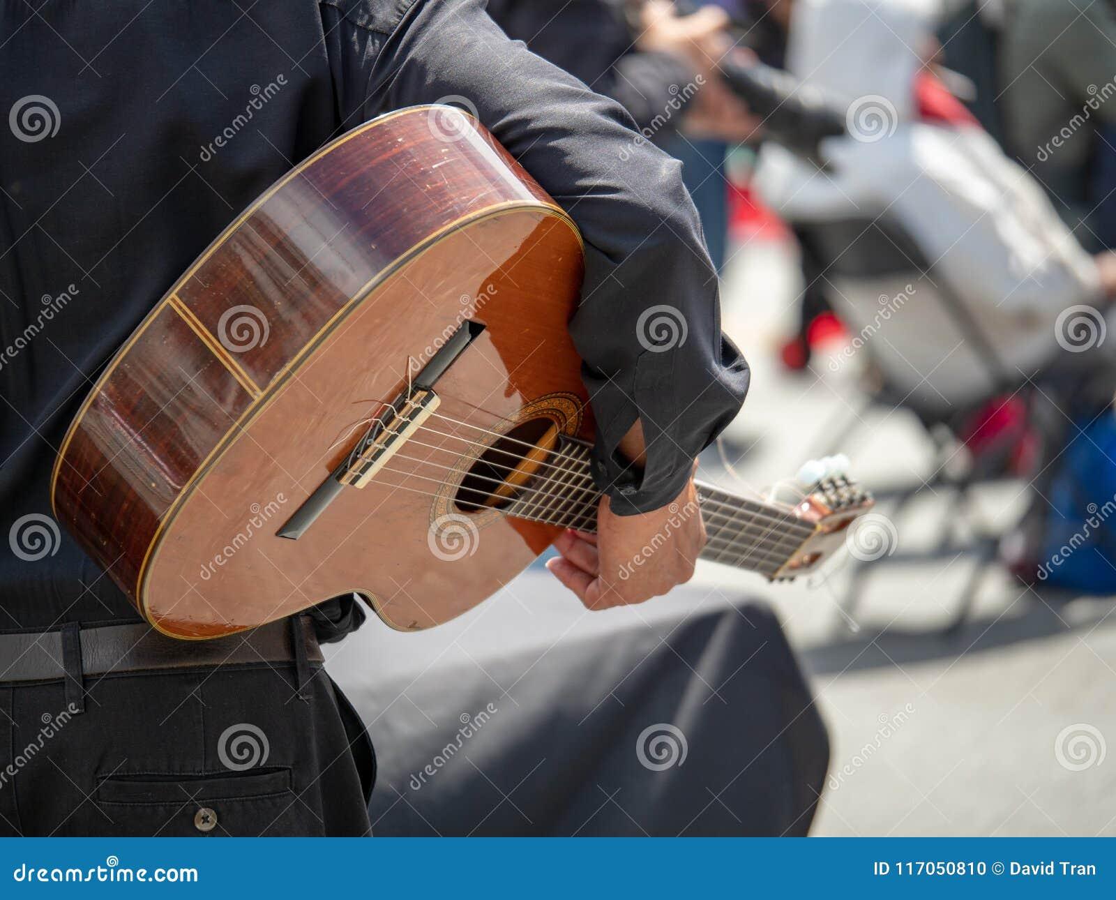 Équipez bercer la guitare à un festival de rue avant une représentation