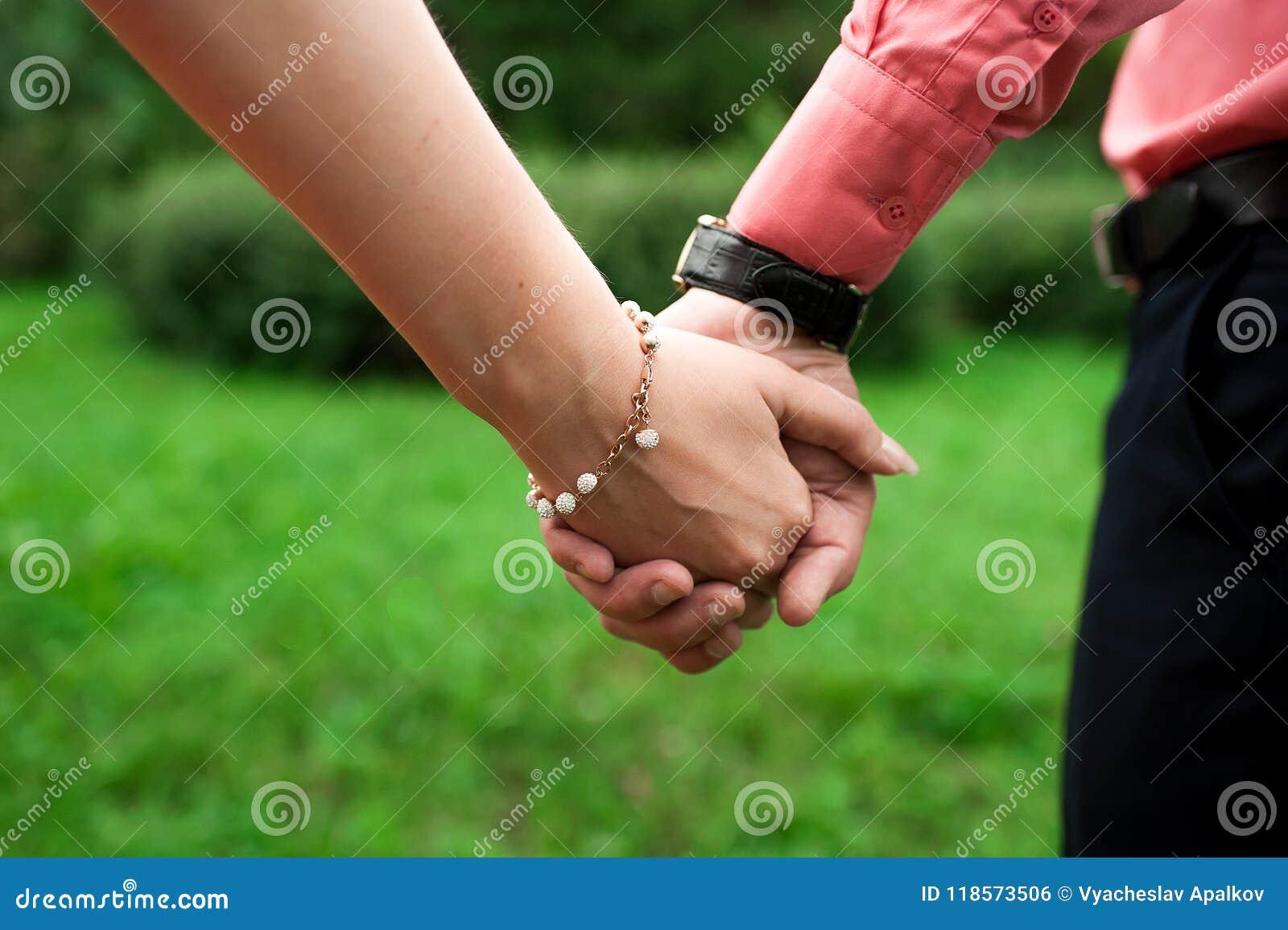 Équipez et une femme avec un bracelet tenant des mains étroitement