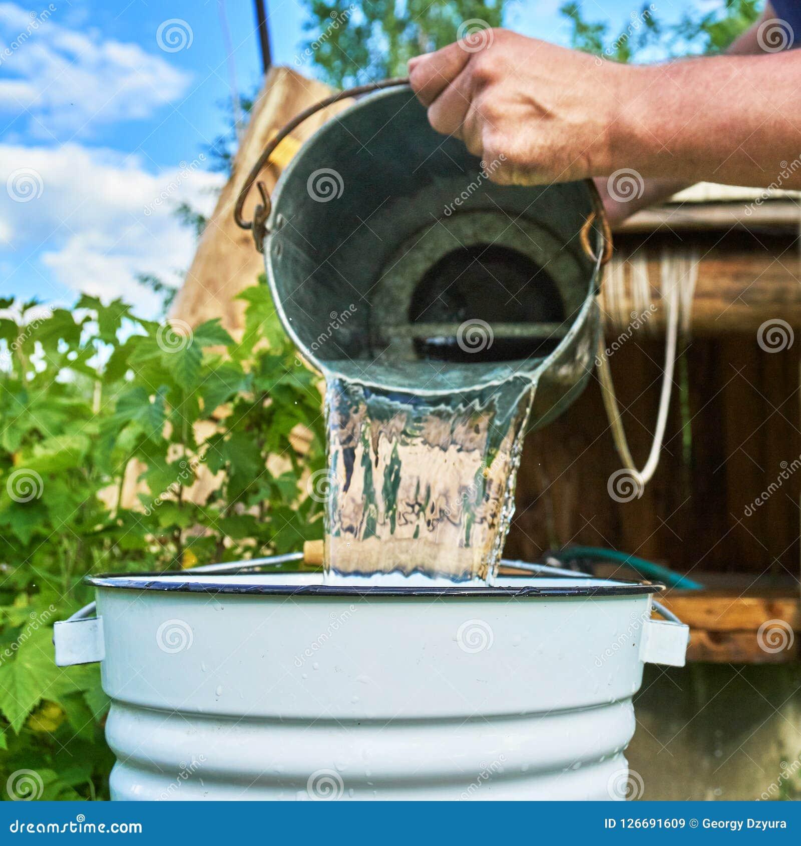 Équipez l eau de versement juste prise de l bien dans un seau émaux