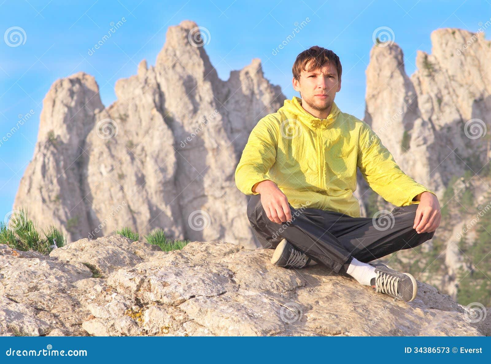 Équipez la méditation de détente de yoga de voyageur se reposant sur des pierres avec Rocky Mountains