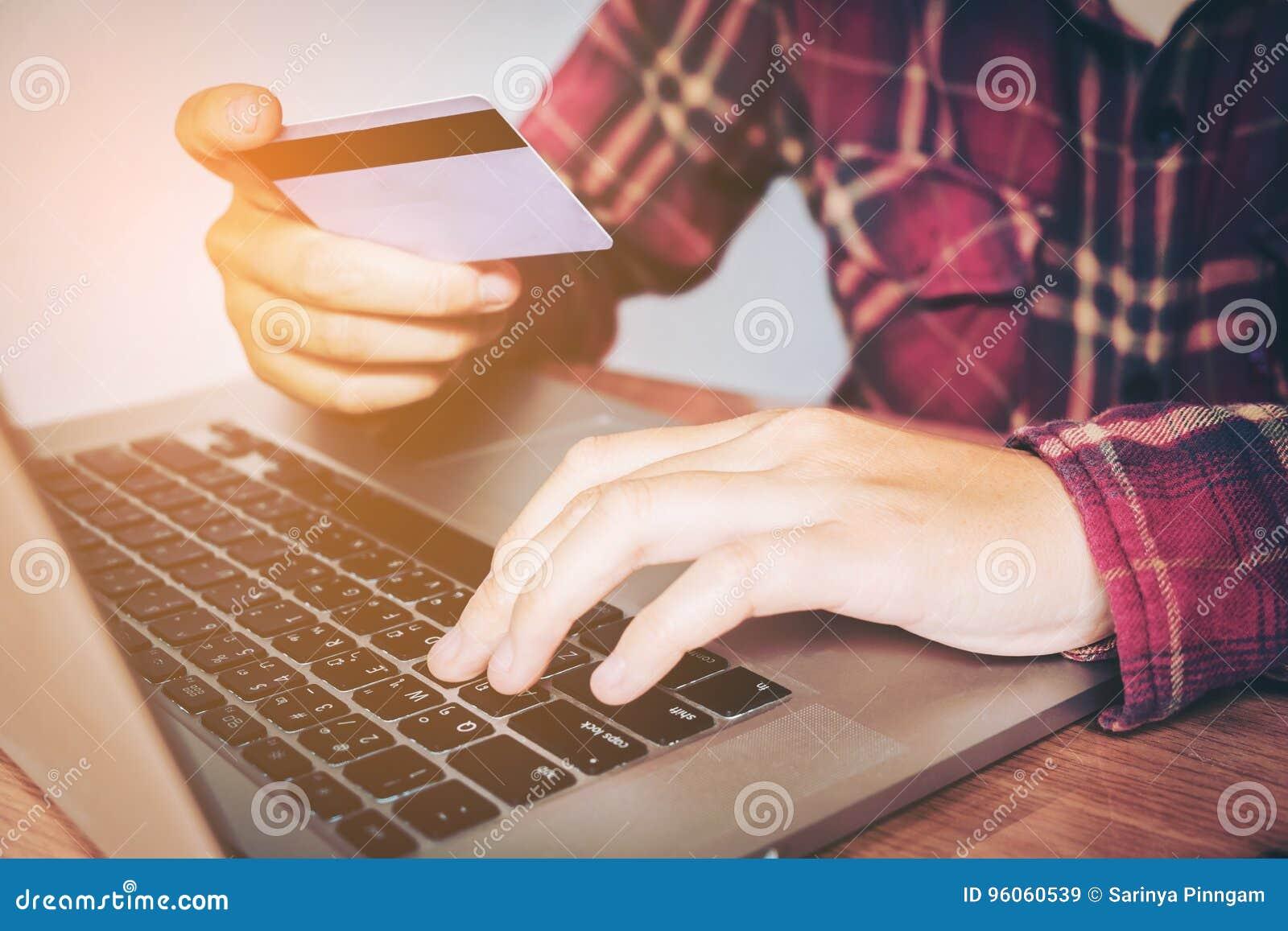 Équipez la main tenant la carte de crédit utilisant la banque en ligne d ordinateur portable de clavier