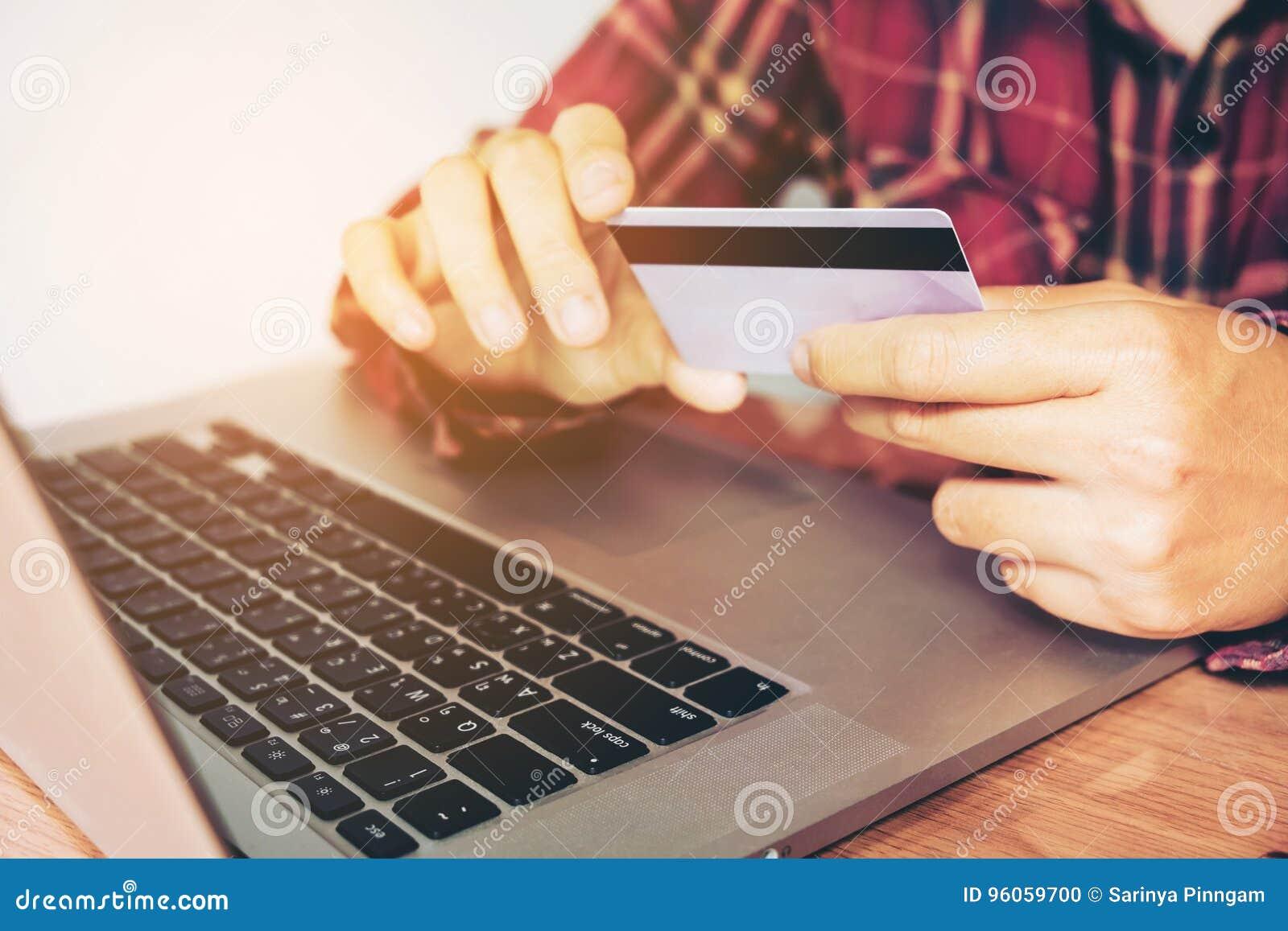 Équipez la main tenant le smartphone et la carte de crédit faisant des opérations bancaires en ligne