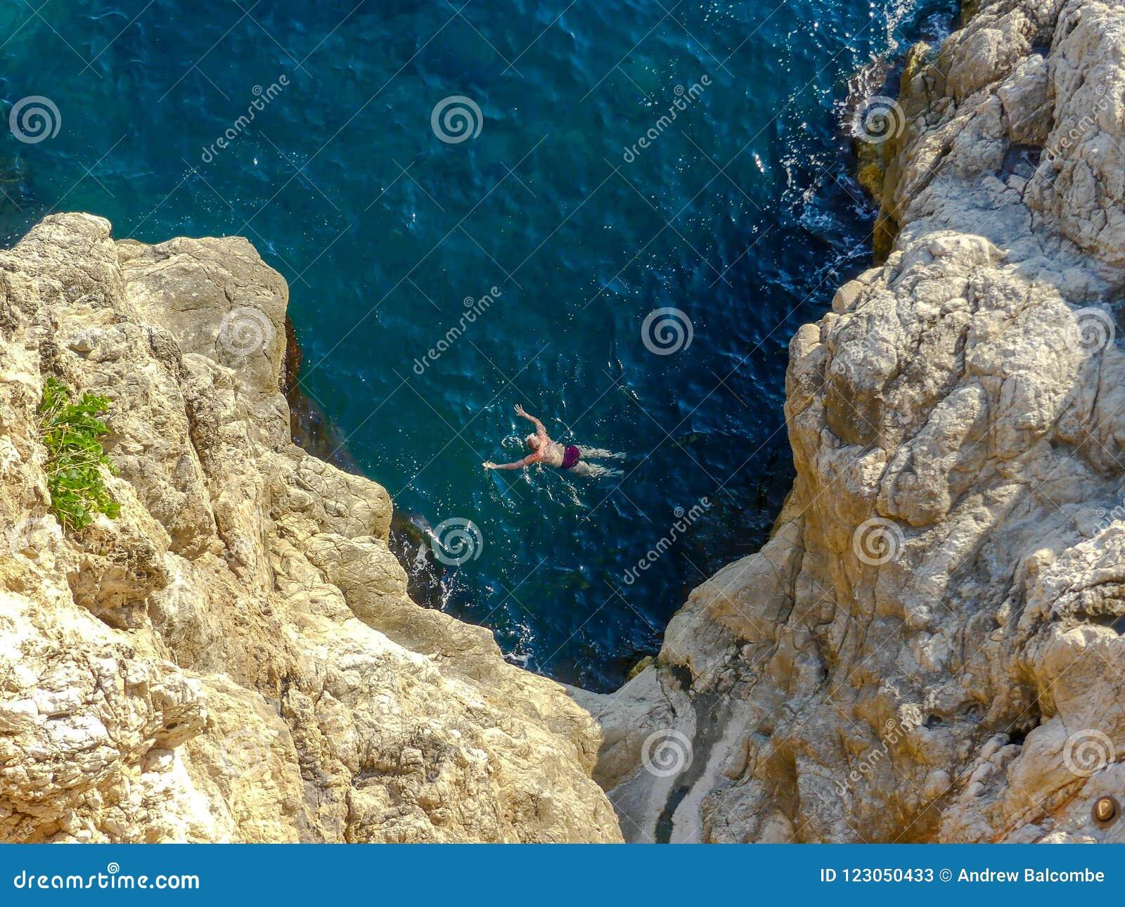 Équipez la natation en eau libre près des falaises en dehors des vieux murs de ville de Dubrovnik
