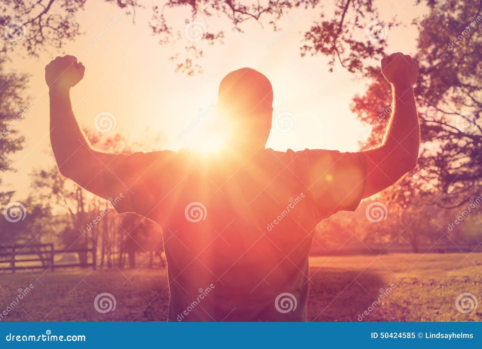 Équipez la position avec des bras augmentés dans le geste de victoire
