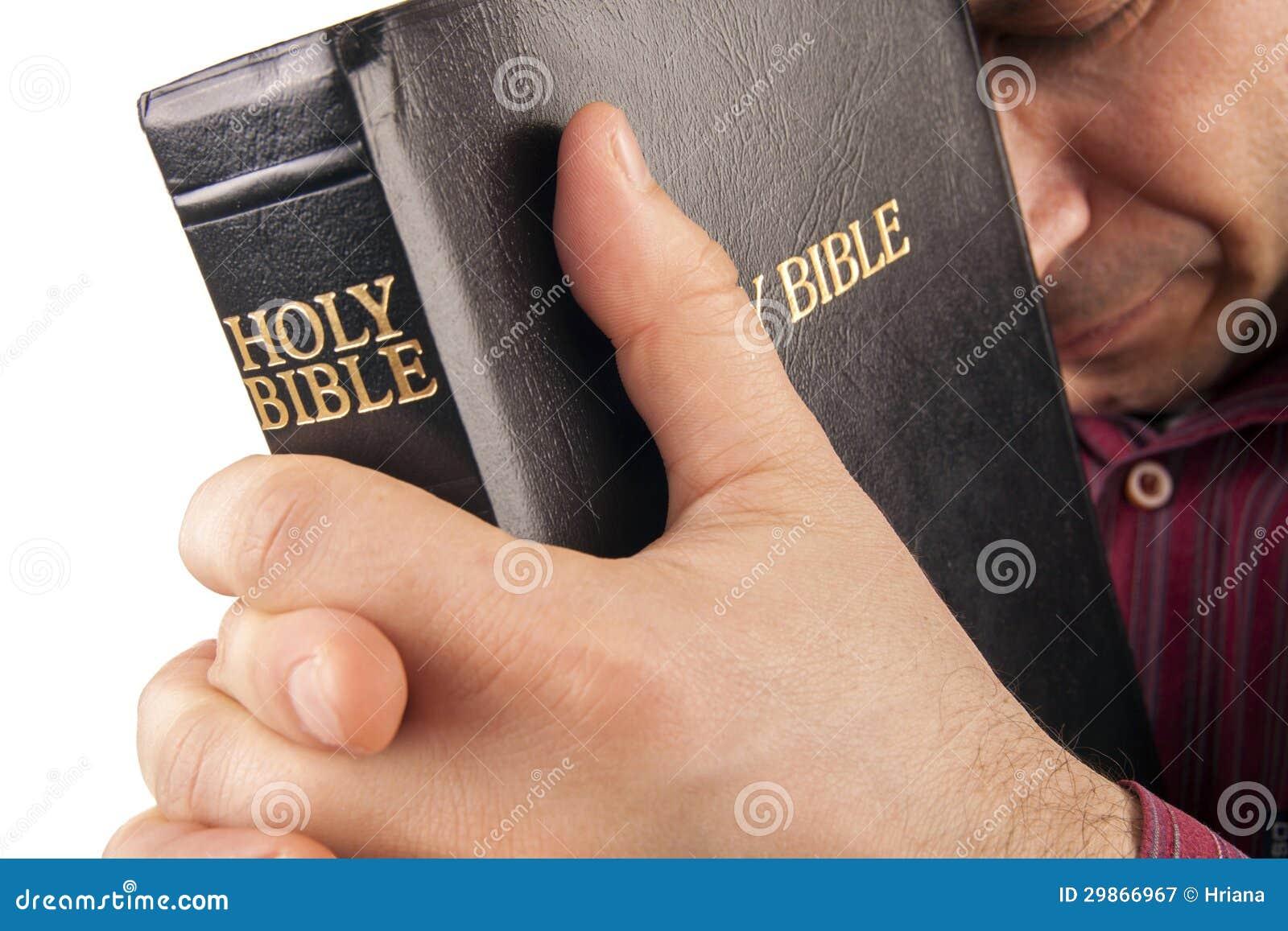 Homme priant tenant la bible